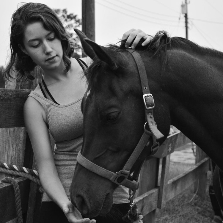 Equestrian Adventuress S. D. petting a horse's head and nose.