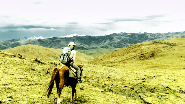 Riding through the mountains with a backpack and saddle packs.