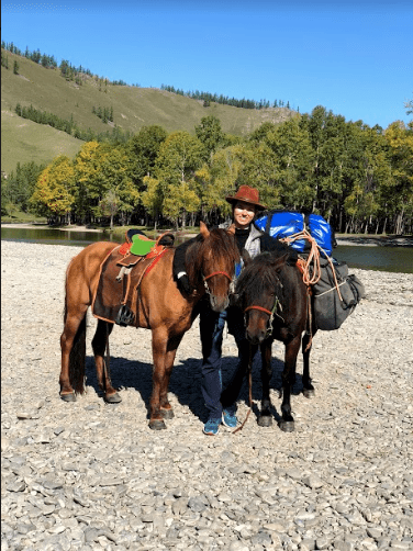 Two Mongolian horses one with saddle one with packs accompany me on my Horse Riding Trip in Mongolia