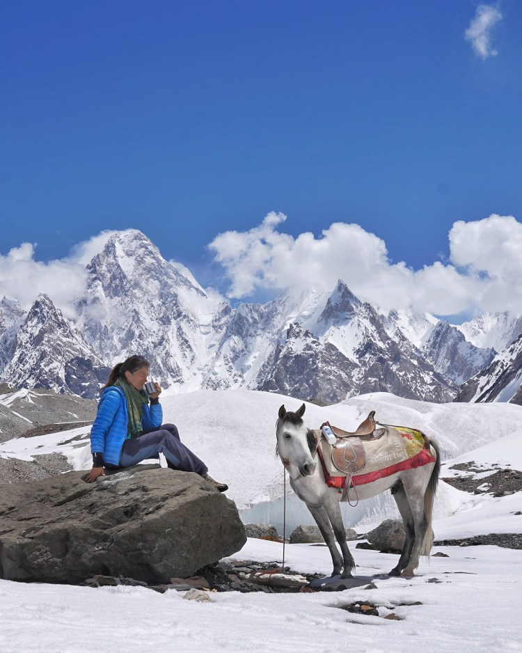 A woman and a horse are resting during a horse riding trip in the mountains in Pakistan