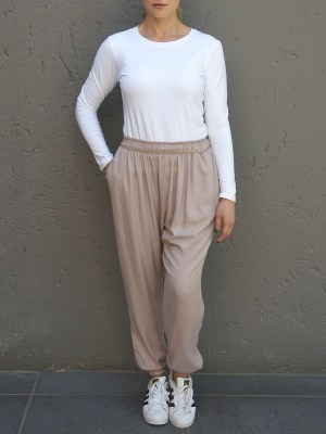 Beige slouchy joggers with a white long sleeve top
