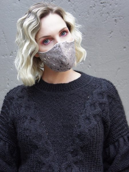 Model wear black knit top with neutral sequins silver face mask