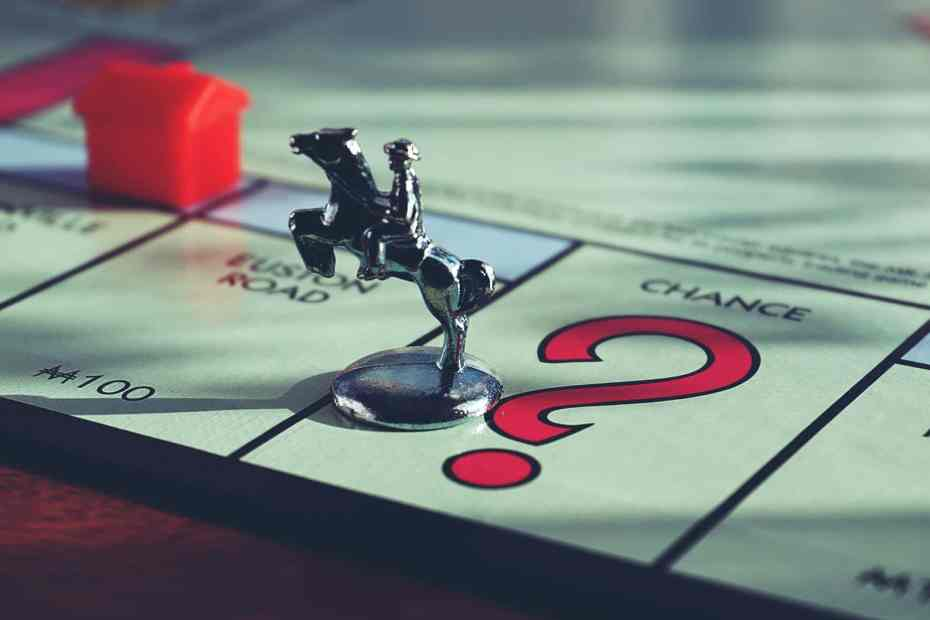 horse miniature toy on top of monopoly board game. Horse themed board game
