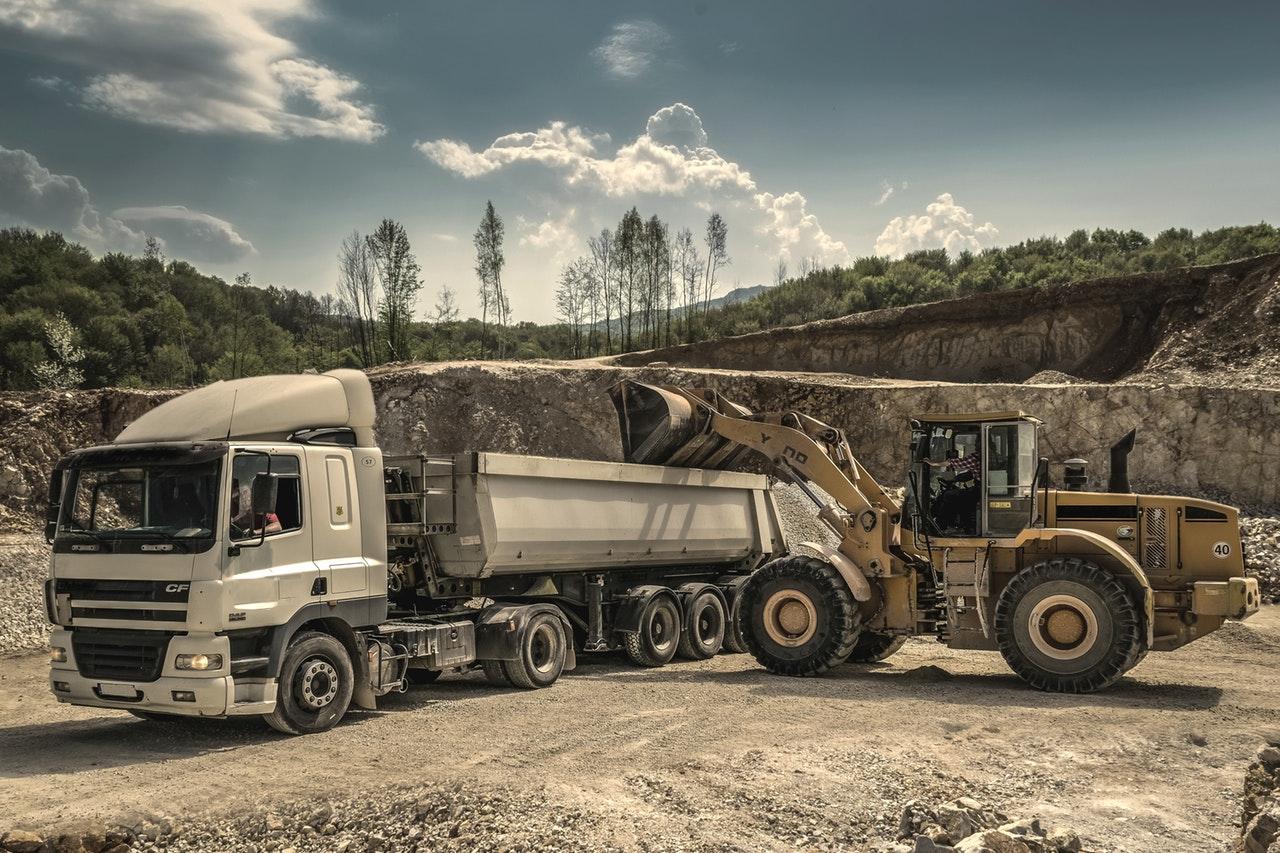 Front load loader beaside white dump truck