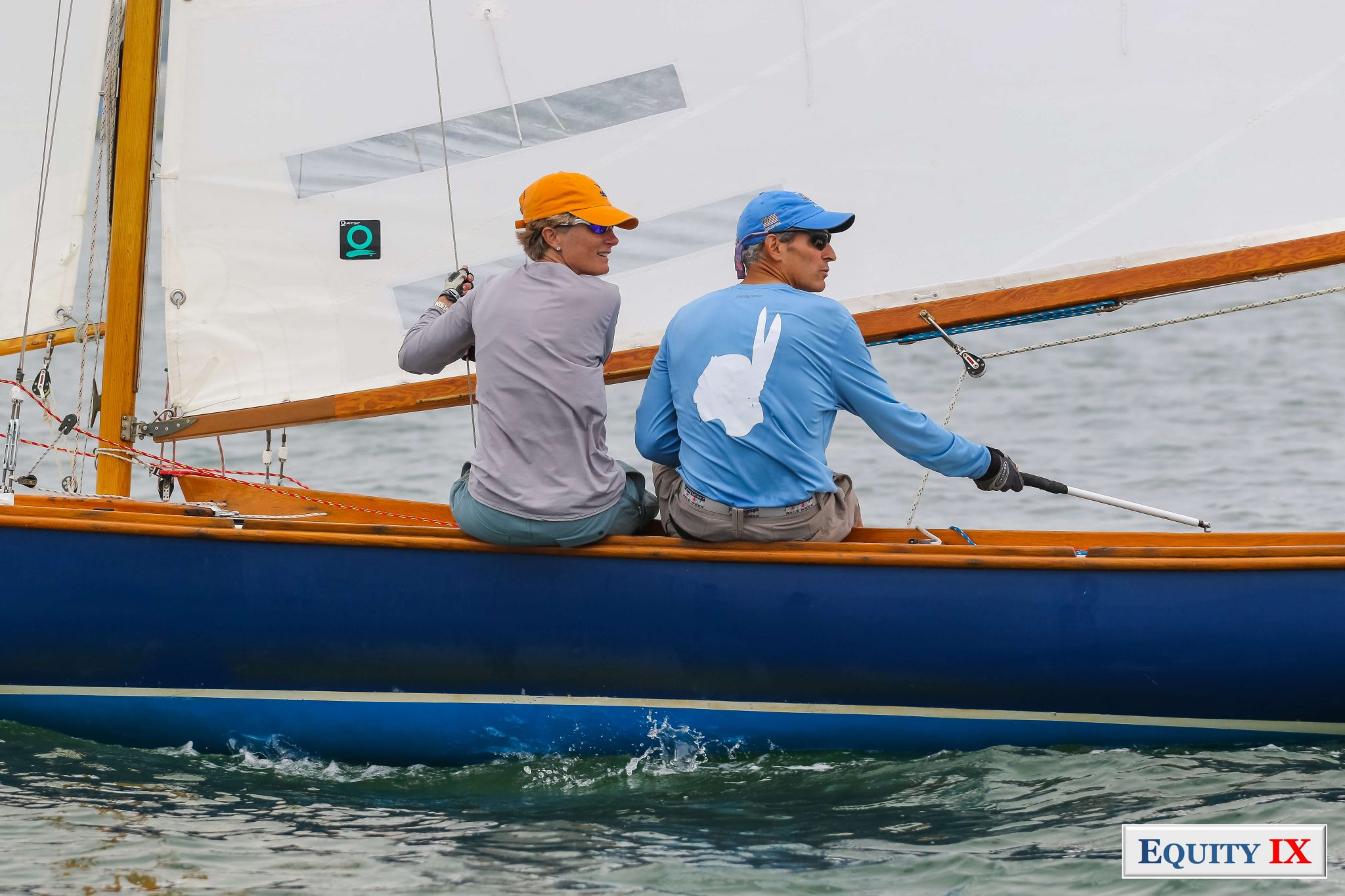 Indian fleet boat #36 Weweeder - helm Gregory Fowlkes and wife Annabelle hiking out of side of boat with yellow hat and sunglasses - Gregory has blue hat with matching blue and white Indian shirt - Sailing on Nantucket at Constable Cup - 2017 © Equity-IX - SportsOgram - Leigh Ernst Friestedt - ZyGoSports