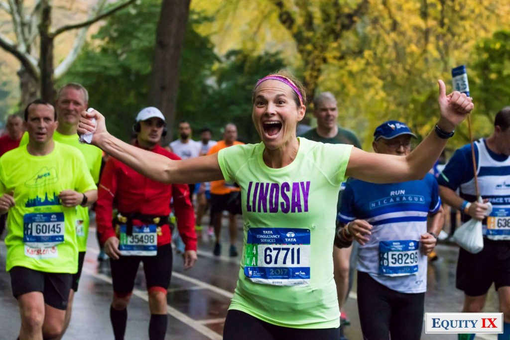 Lindsay Ernst running with her hands up and a huge smile on her face in 2017 NYC Marathon - Mile 25 in Central Park © Equity IX -SportsOgram - Leigh Ernst Friestedt - ZyGoSports