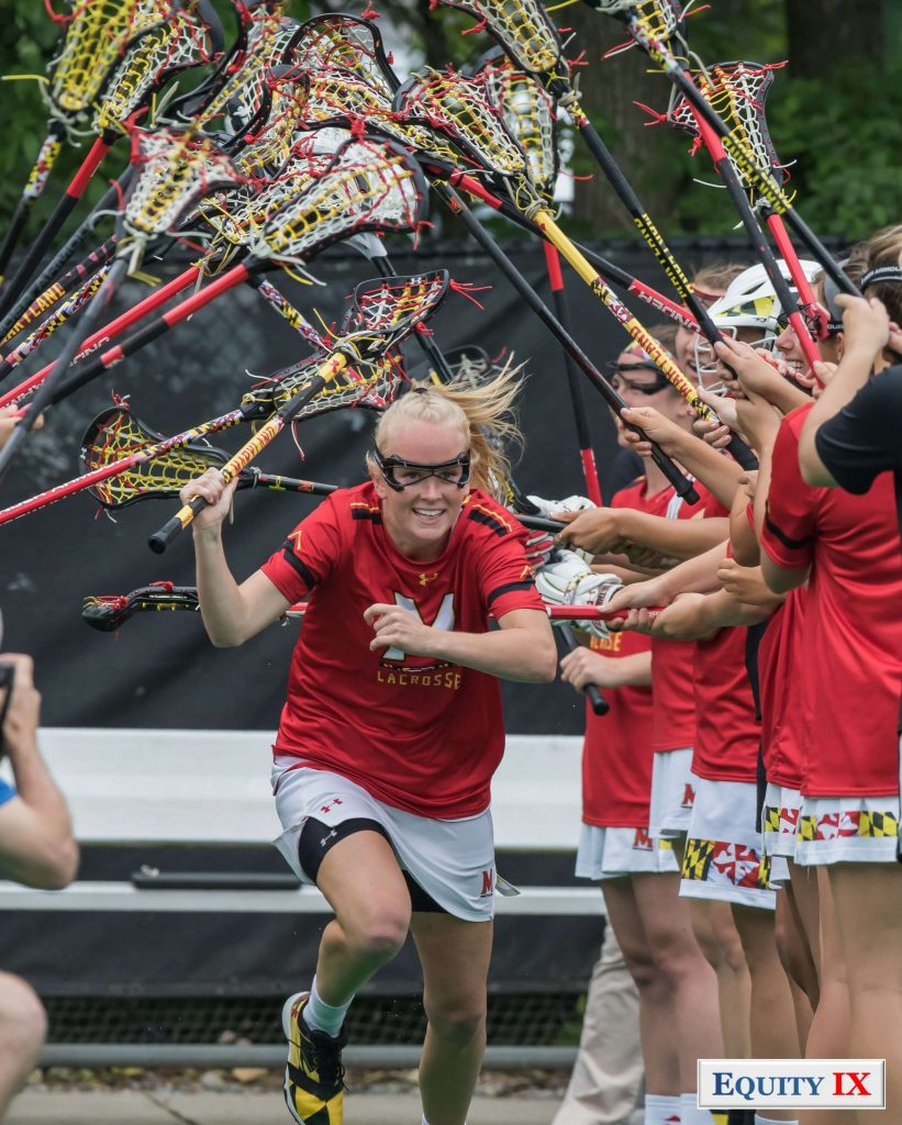 #11 Caroline Steele runs through a line of women's lacrosse sticks at the NCAA Women's Lacrosse Quarterfinals - she has a huge smile on her face with googles on and bright red Maryland shirt with matching lacrosse stick © Equity IX - SportsOgram - Leigh Ernst Friestedt