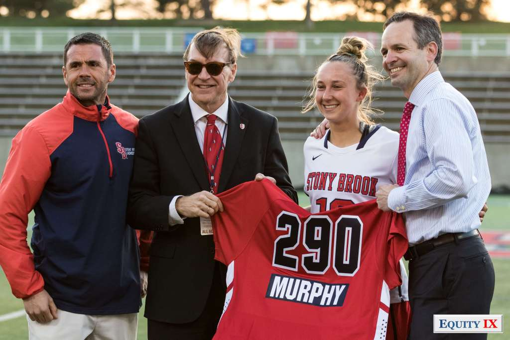 "#18 Courtney Murphy celebrates scoring 290 goals at Stony Brook with a bright read jersey with ""290"" and ""Murphy"" on back - Head Coach Joe Spallina, Athletic Director and President of Stony Brook - 2018 NCAA Women's Lacrosse © Equity IX - SportsOgram - Leigh Ernst Friestedt - ZyGoSports"