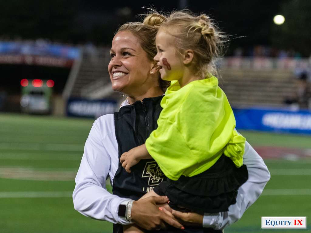 Boston College Head Coach, Acacia Walker, celebrates with daughter after win against Maryland at 2018 Women's Lacrosse Final Four © Equity IX - SportsOgram - Leigh Ernst Friestedt - Photo by Margaret Hyatt