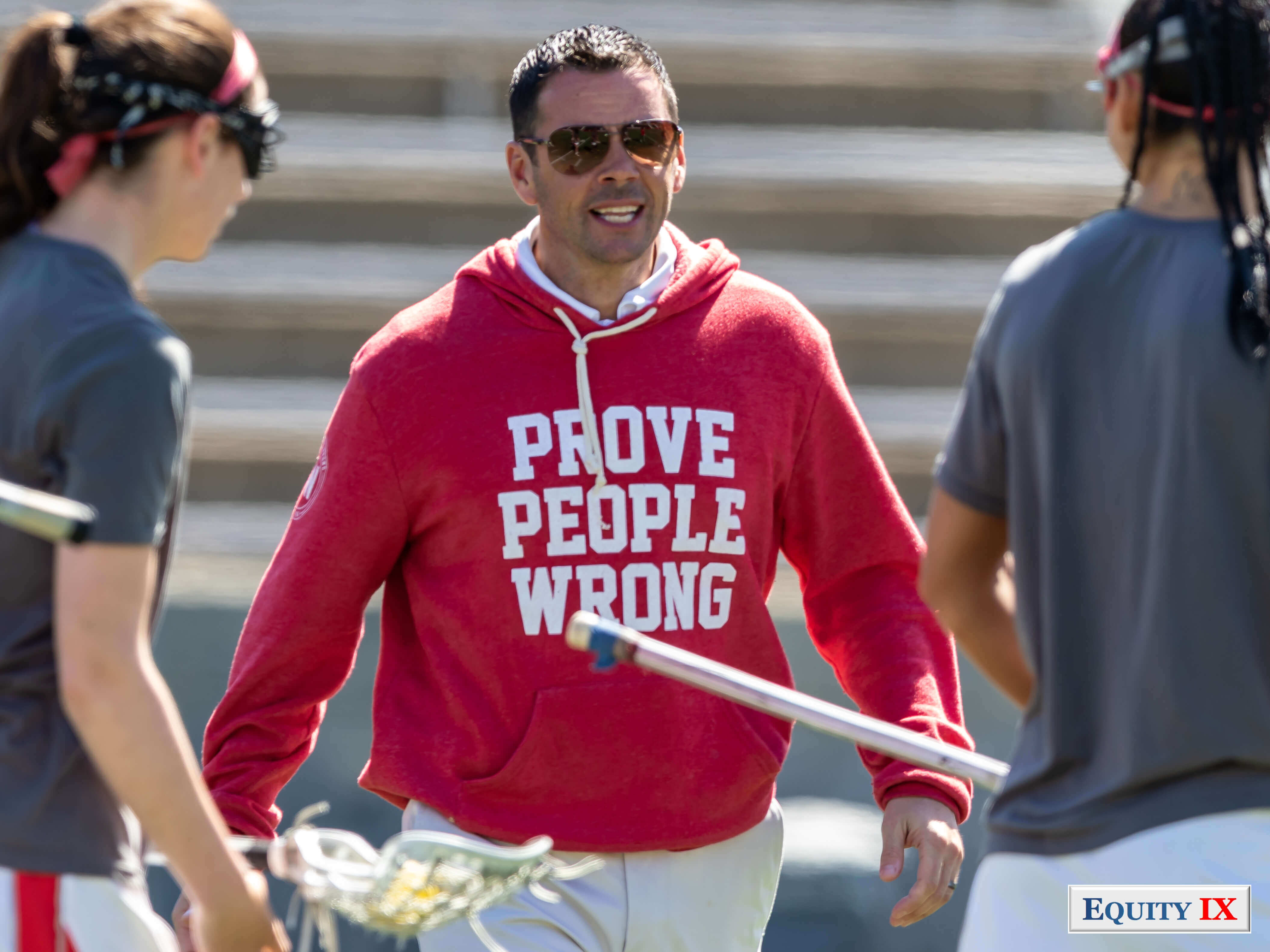 Joe Spallina - Head Coach of Stony Brook wears a red Prove People Wrong sweatshirt during warmup before a game to inspire his team to a NCAA title © Equity IX - SportsOgram - Leigh Ernst Friestedt