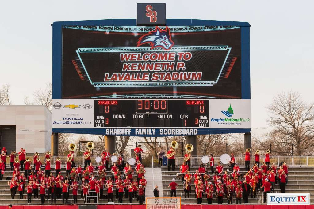 """Stony Brook scoreboard with band in the stands says """"Welcome to Kenneth P. Lavalle Stadium"""" Score is Seawolves 0 Blue Jays 0 1st quarter with 30 minutes to play and three times out left for both teams © Equity IX - SportsOgram - Leigh Ernst Friestedt"""