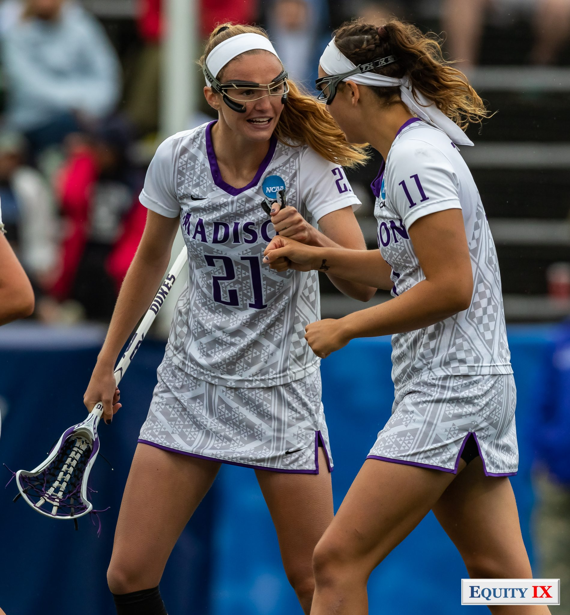 """Maddie McDaniel (JMU #11) and Morgan Hardt (JMU #21) pump fists to celebrate a goal both are wearing goggles and whit headbands with """"Madison"""" and """"NCAA"""" logos on their jerseys - 2018 NCAA Women's Lacrosse Championship Game © Equity IX - SportsOgram - Leigh Ernst Friestedt"""