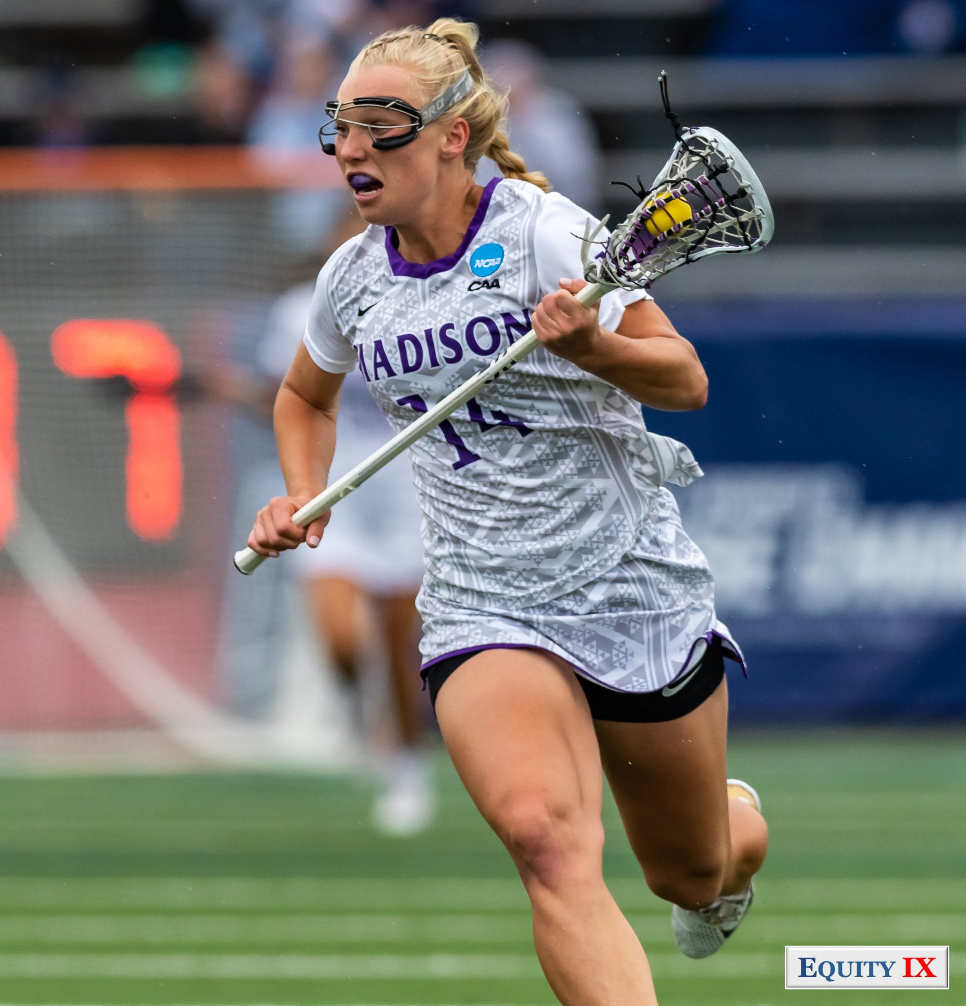 """Kristen Gaudian (JMU #14) cradles the yellow ball left handed going to goal with goggles and purple JMU mouthguard, """"Madison"""", """"NCAA"""" and """"CAA"""" logos on her jersey - 2018 NCAA Women's Lacrosse Championship Gam - Tewaaraton Finalist © Equity IX - SportsOgram - Leigh Ernst Friestedt"""