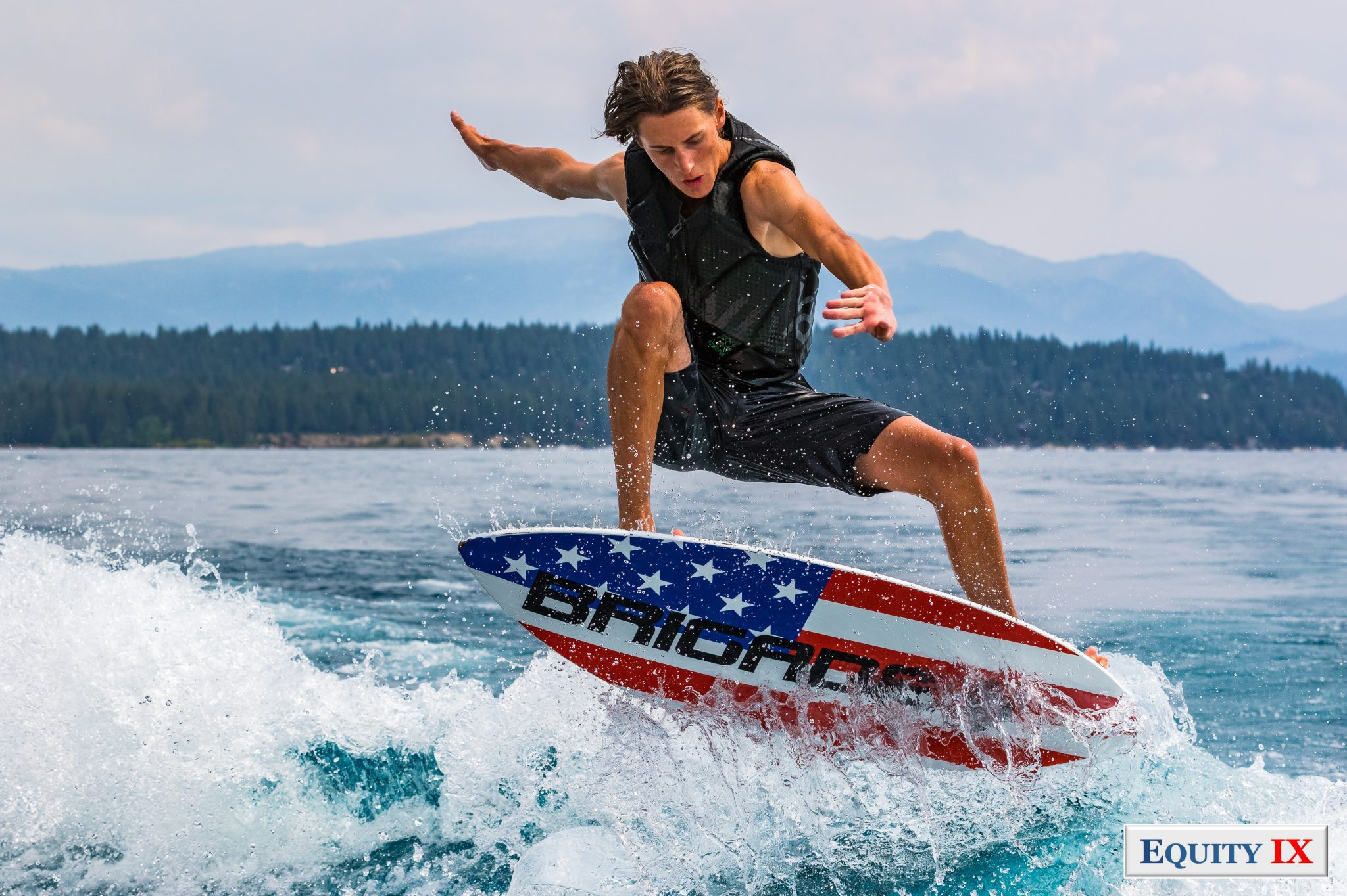 Cole Sorensen wakesurig with his red white and blue Brigade board out of the water, his ripped arms fully extended from his back life jacket - 2018 Tahoe Surf Company @ Equity IX - SportsOgram - Leigh Ernst Friestedt