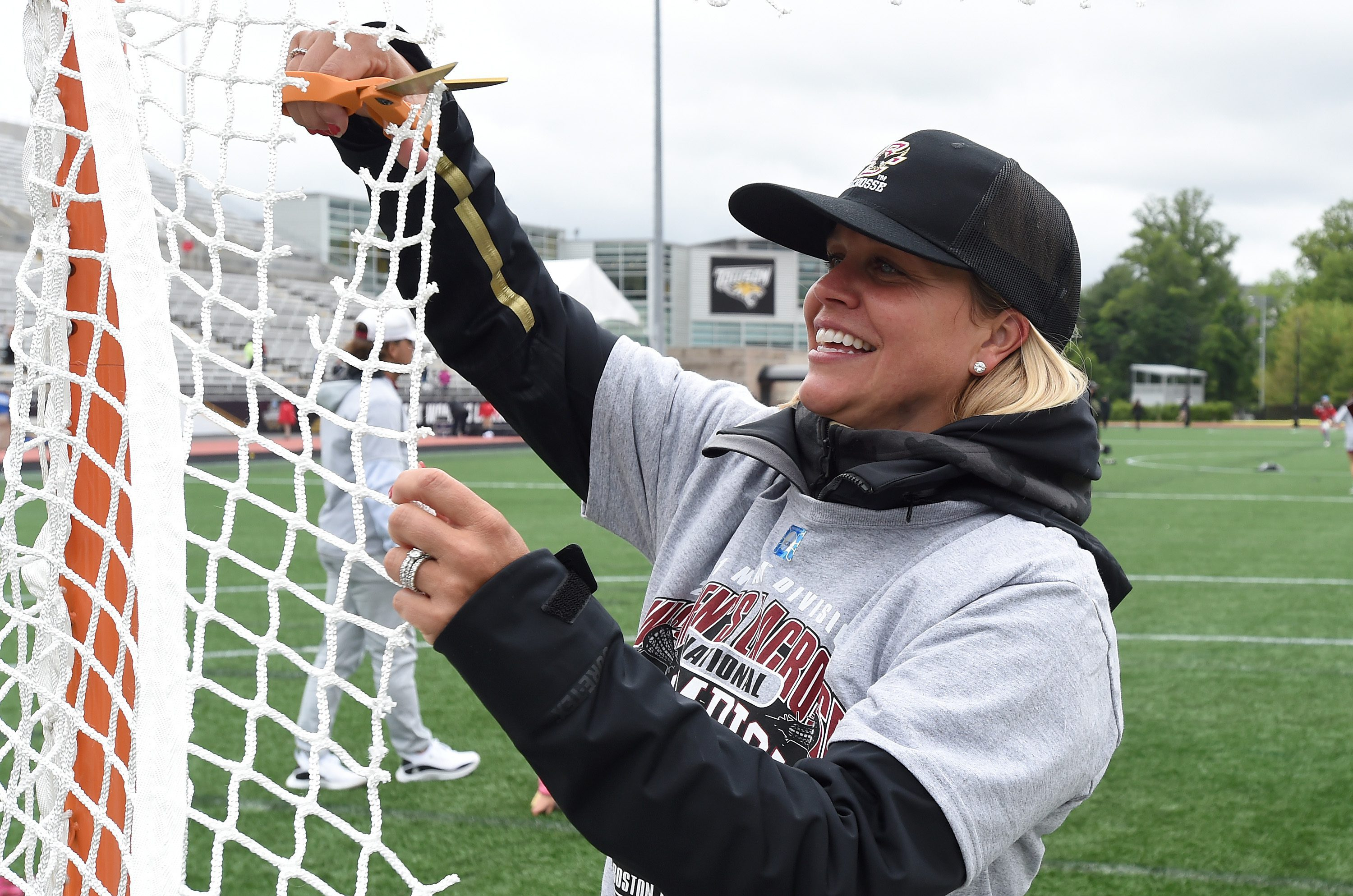 Boston College Head Coach - Acacia Walker-Weinstein cuts lacrosse goal net with scissors after winning 2021 NCAA Women's Lacrosse Championship with a big smile, BC Lacrosse hat and National Championship shirt © Equity IX - SportsOgram - Leigh Ernst Friestedt