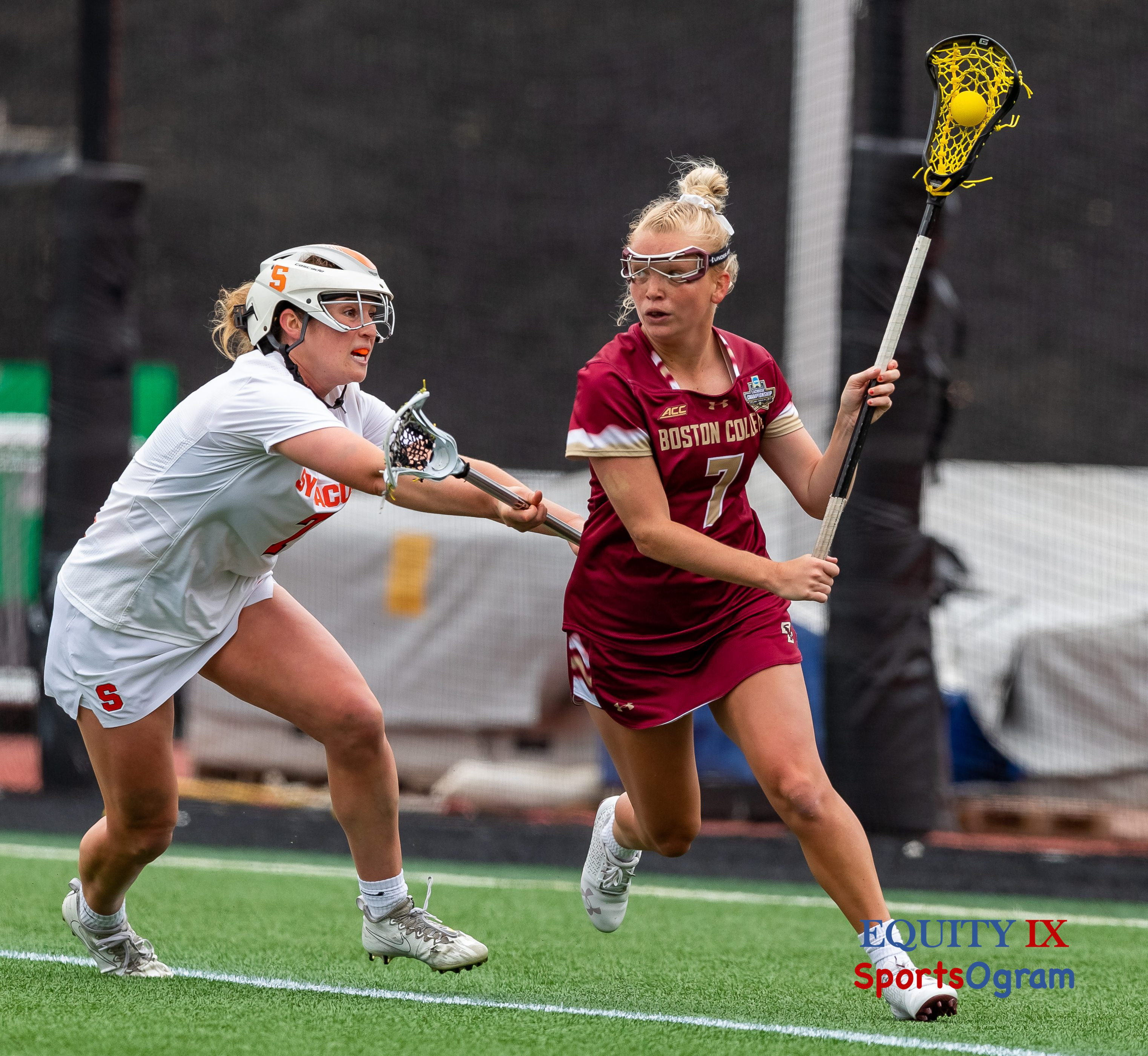 #7 Caitlynn Mossman (Boston College) looks to pass the yellow lacrosse ball left handed wearing goggles from behind the cage with #7 Kerry Defliese (Syracuse) wearing a helmet with bright orange S on side - 2021 NCAA Women's Lacrosse Championship Game © Equity IX - SportsOgram - Leigh Ernst Friestedt