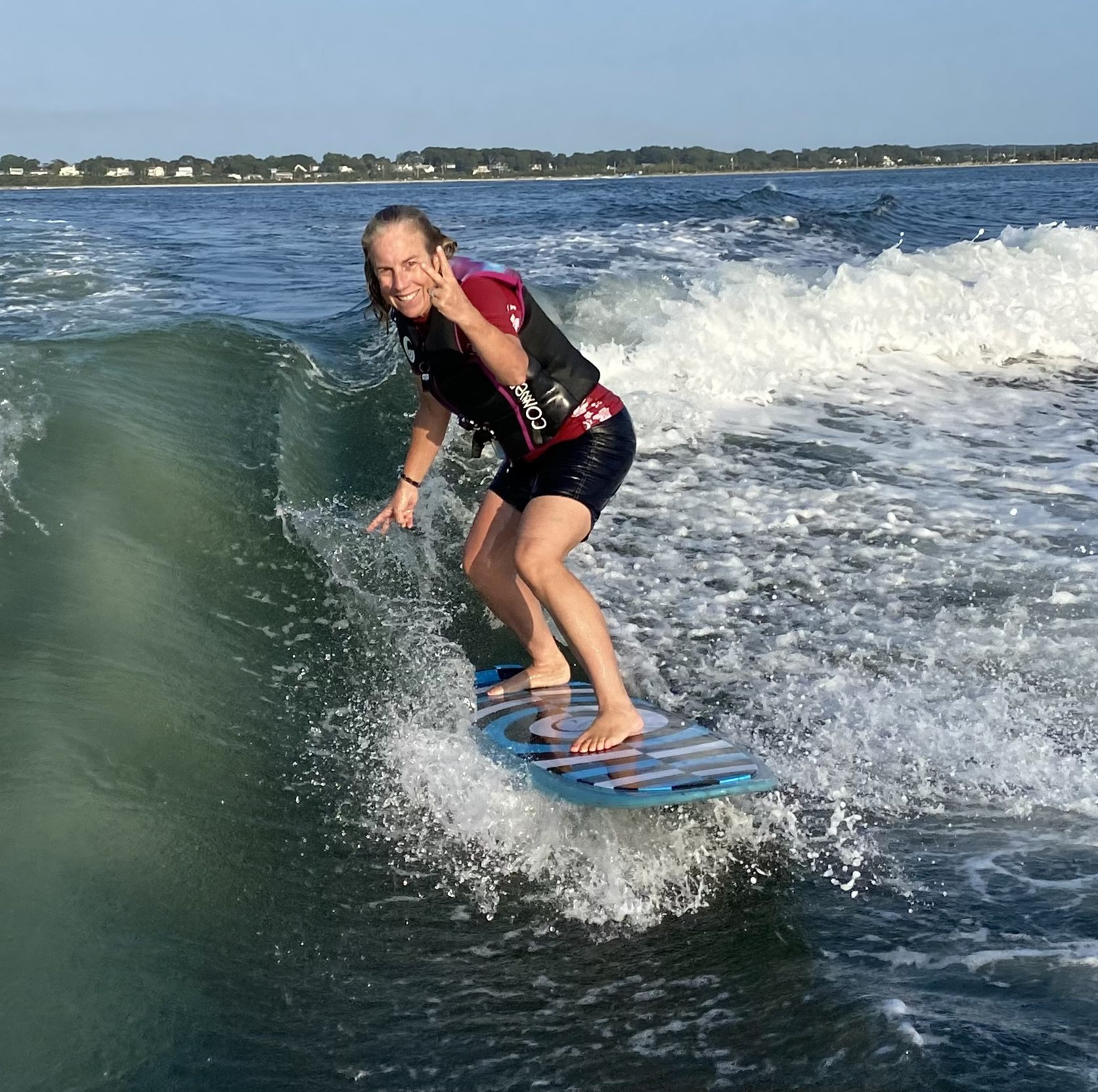 Leigh Ernst Friestedt wake surfing in the Hamptons with a blue surfboard and red surf guard and life jacket - smiling and two fingers raised and ocean in background © Equity IX - SportsOgram
