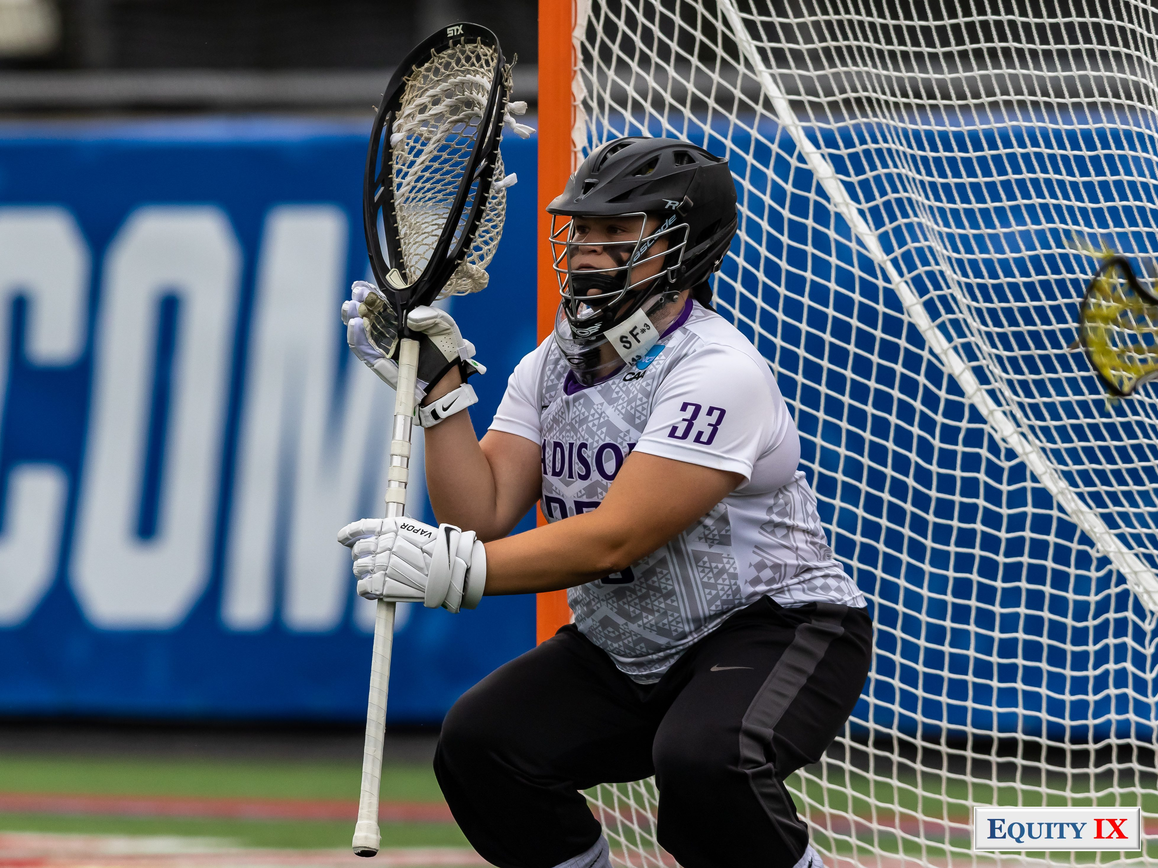 #33 Molly Dougherty (JUM Goalie) stand crouched down in lacrosse goal wearing a black helmet and holding onto an oversized lacrosse stick in preparation to stop a free position shot - 2018 NCAA Women's Lacrosse Championship Game © Equity IX - SportsOgram - Leigh Ernst Friestedt