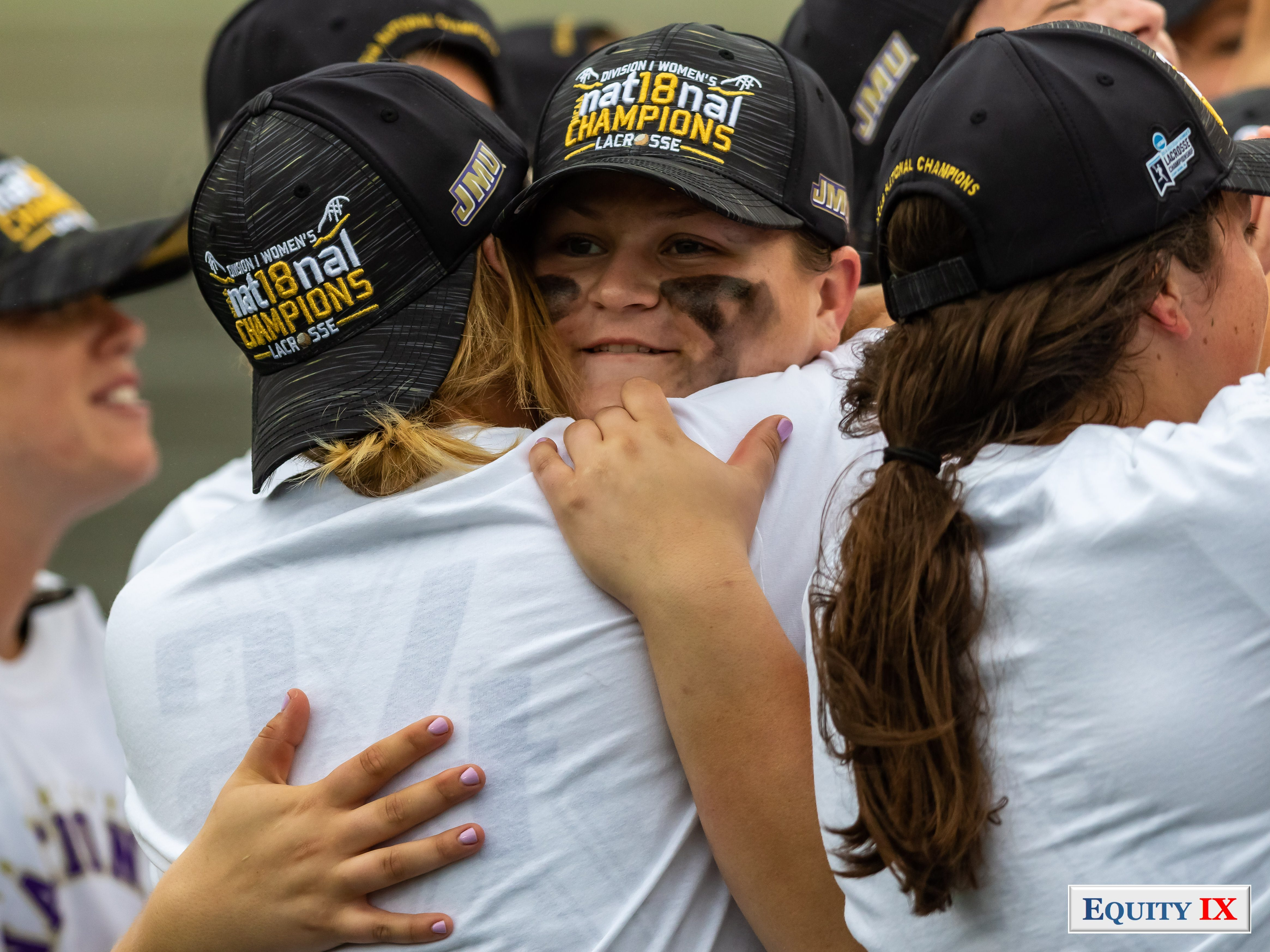 """#33 Molly Dougherty (JMU Goalie) hugs MU teammate after winning national title both female players are wearing black and gold """"JMU NCAA Division I Women's Lacrosse National Champions"""" baseball hats, Molly has smudged eyeblack on her cheeks - 2018 NCAA Women's Lacrosse Champions © Equity IX - SportsOgram - Leigh Ernst Friestedt"""
