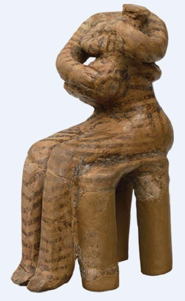 Πήλινο ειδώλιο Κουροτρόφου από τη Θεσσαλία. Λείπει το κεφάλι. Η γυναίκα κάθεται σε σκαμνί και κρατάει στην αγκαλιά της βρέφος. Όλη η μορφή είναι διακοσμημένη με απλές γραμμές και σπείρες. (Μουσείο Βόλου)