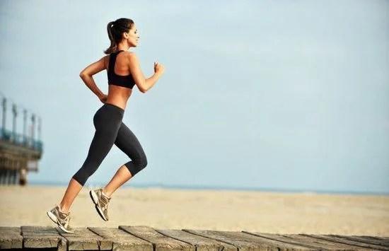 Chica corriendo al lado de la playa.
