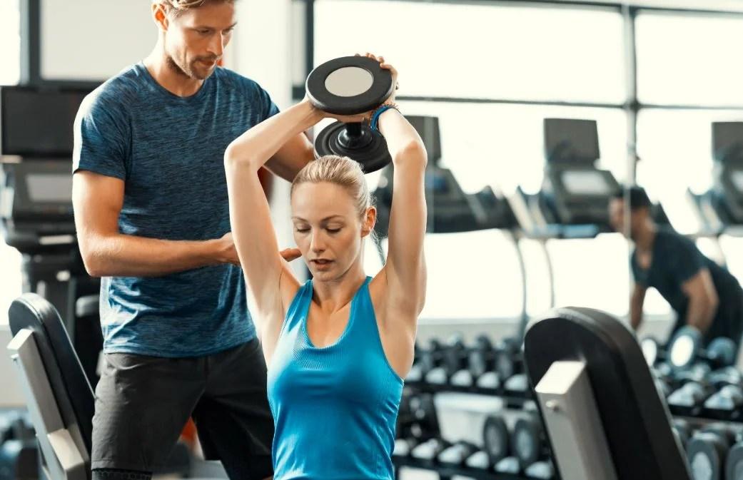 Chica haciendo un ejercicio con pesas para la espalda.
