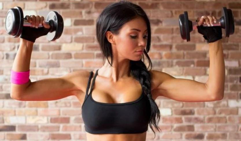 Una chica hace ejercicio con pesas.