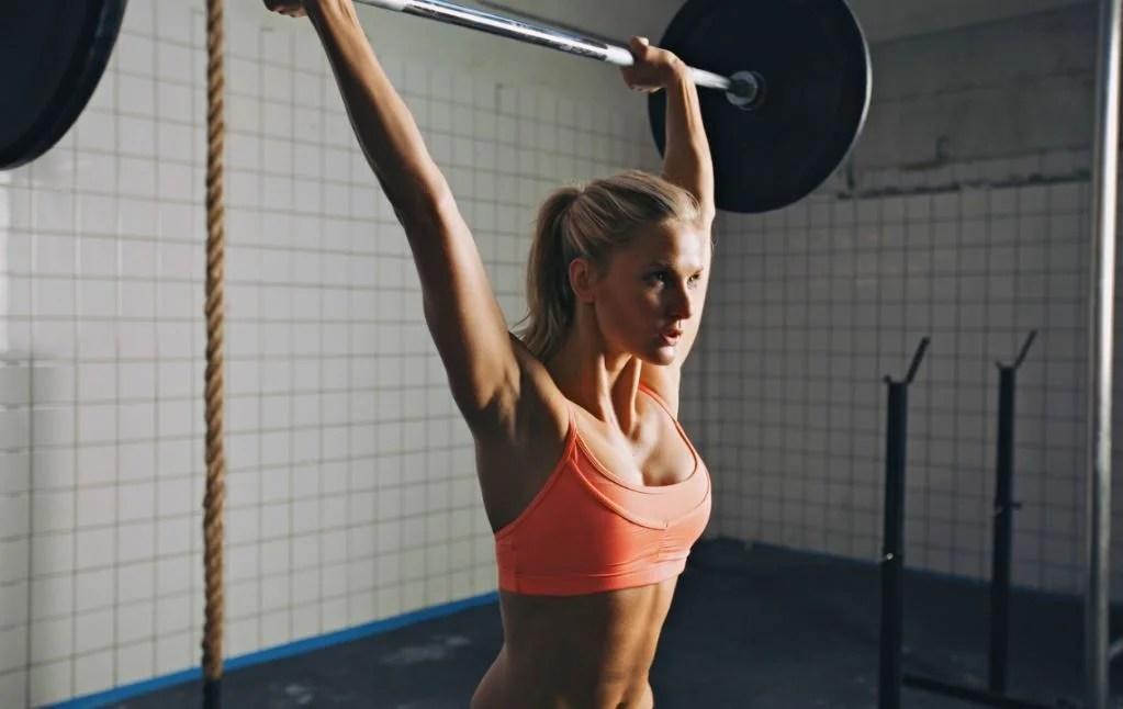 Chica haciendo esfuerzo levantando pesas.