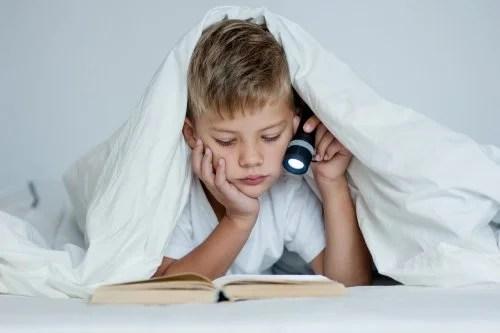 Niño estudiando en la cama, uno de los peores hábitos de estudio.