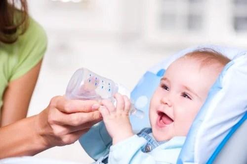 Madre empezando a ofrecerle agua a su bebé en un biberón.