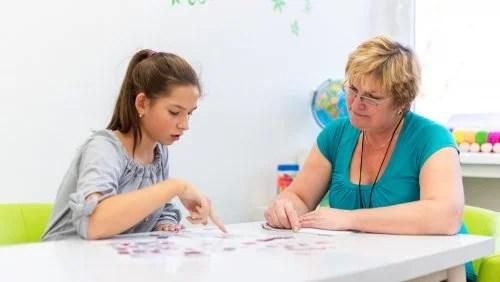 Niña con una profesora de apoyo para mejorar en sus dificultades de aprendizaje.