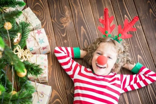 Niño con orejas y nariz de reno tumbado debajo del árbol de Navidad.