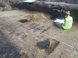 Een drietal, deels uitgegraven paalsporen die een deel van een gebouw vormen. foto: Gemeente Breda