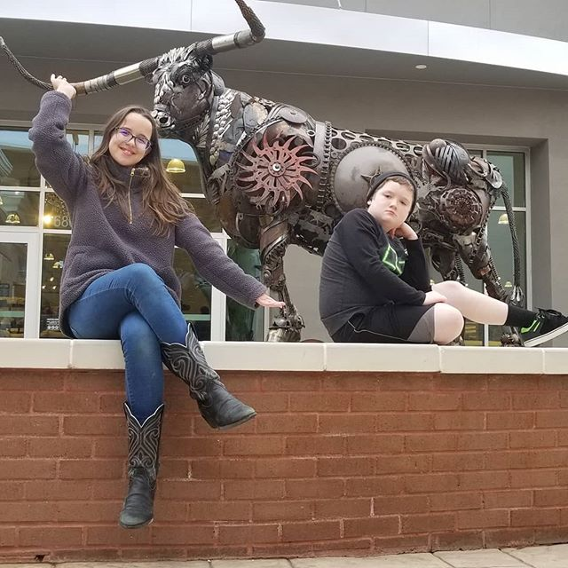 Both of the kids wanted a picture in front of this bull