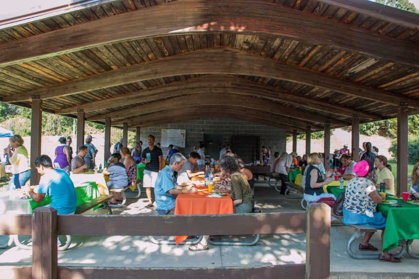 A photo of a group of people sitting under an outdoor gazebo, eating plates of food.