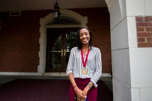 In the photo, a young Nigerian woman (Nneoma Nwankwo) stands with her hands clasped on the steps of a brick building. She is wearing a medallion that recognizes her as an Honors student.