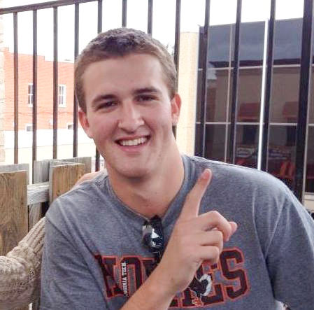 """In the photo, a young man (Colin Moore) smiles and poses for a picture with one hand pointing up toward the sky to indicate number one. He is wearing a gray t-shirt with the word """"Hokies"""" written in orange and maroon text."""