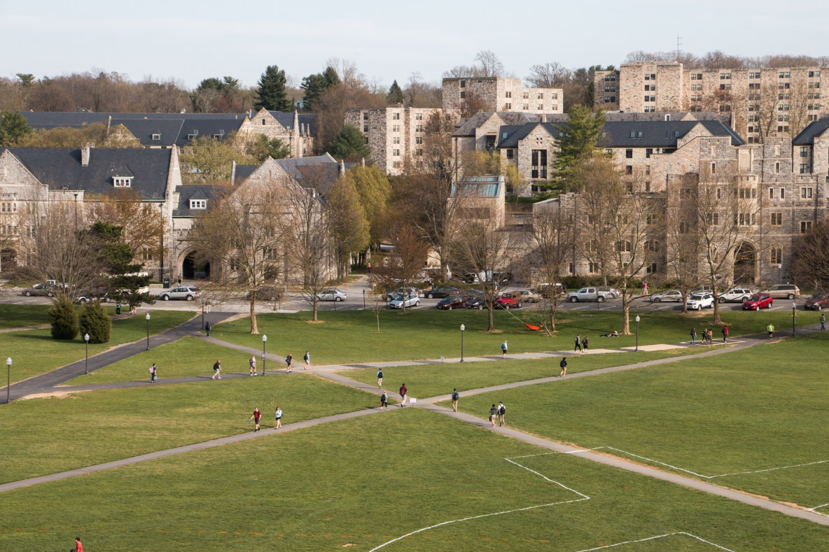 A photo overlooking a green lawn on a college campus with several gray buildings in the background.