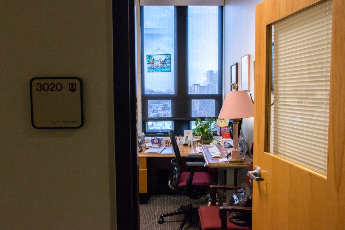 "Photo taken from the outside of a small office. A sign with the name ""Lynn Nystrom"" is visible on the periphery of the photo. Inside the office is a desk and chair and an assortment of knick-knacks like photo frames and a stained glass picture of a horse."