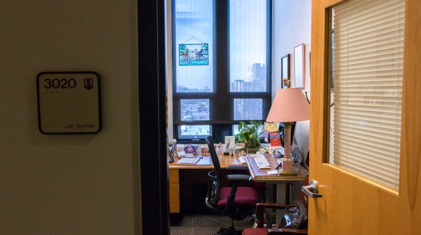 """Photo taken from the outside of a small office. A sign with the name """"Lynn Nystrom"""" is visible on the periphery of the photo. Inside the office is a desk and chair and an assortment of knick-knacks like photo frames and a stained glass picture of a horse."""