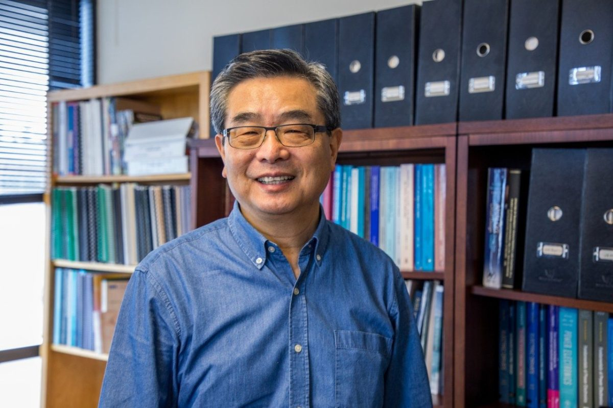A portrait of Fred Lee in his office, in front of full bookshelves.