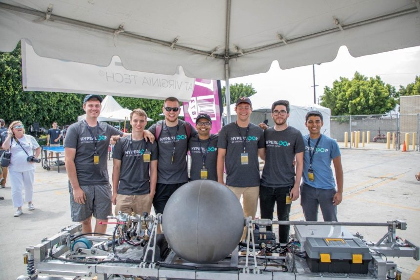 Seven students pose with a Hyperloop pod.