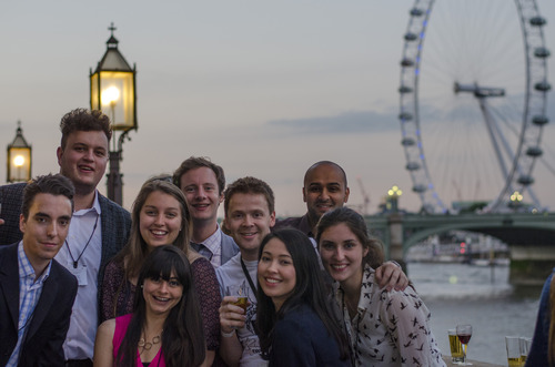 A photo of a group of smiling people standing in front of the London Eye at dusk.