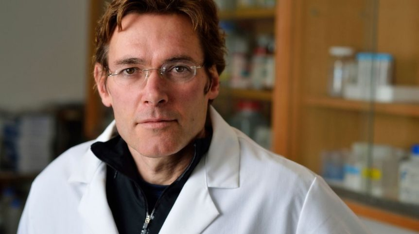 A man, Marc Edwards, poses for a portrait. He is in a lab, wearing a white lab coat.