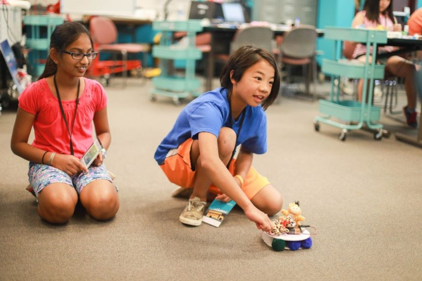 Two young girls sit on the floor with a robot they created that moves across the room.