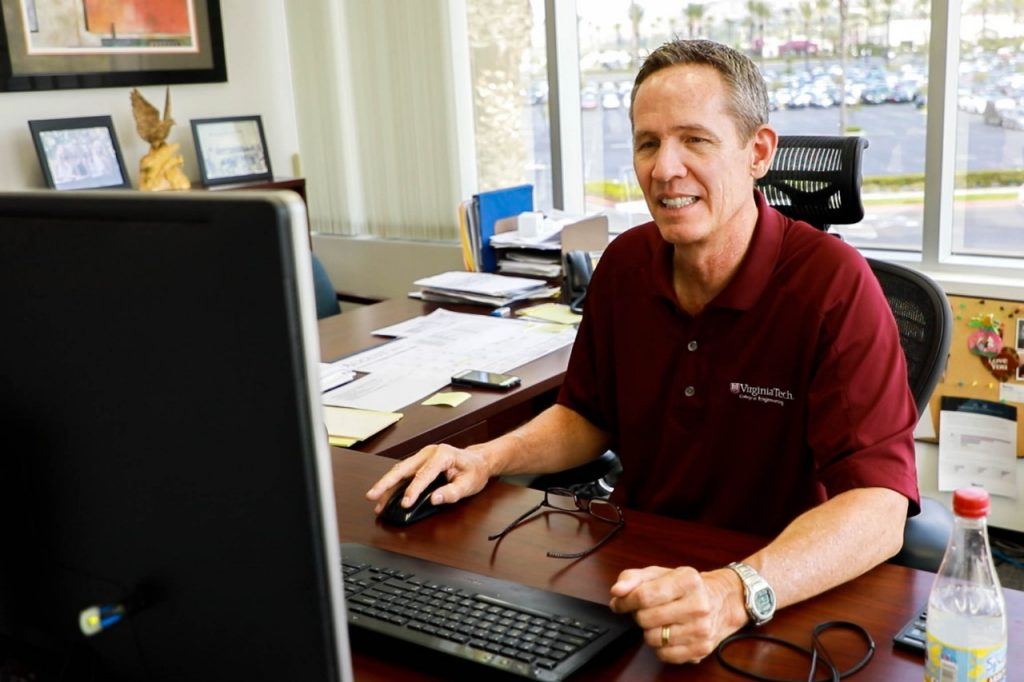 A man sits at a computer and works, wearing a maroon polo shirt that bears a logo from the Virginia Tech College of Engineering.