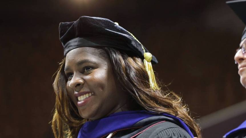 A screenshot of a video still featuring a smiling woman wearing graduation garb.