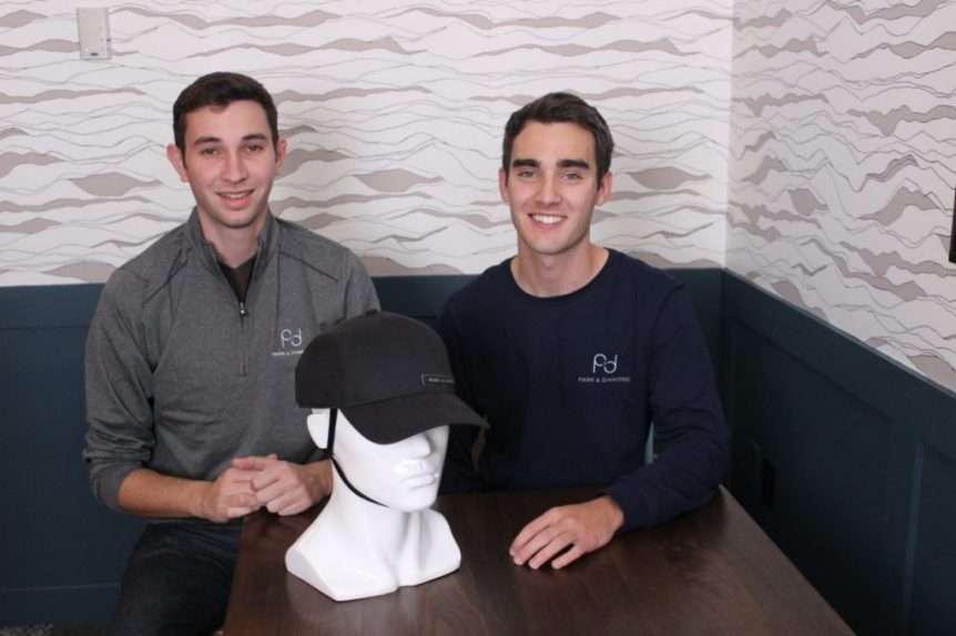 Two young men sit at a table and pose for a photo. On the table is a white mannequin head and neck, wearing a black helmet that looks like a baseball cap.