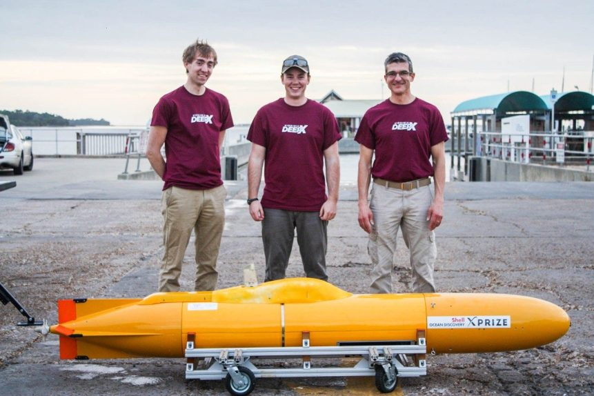 Three men stand behind a small yellow underwater autonomous vehicle and pose with smiles for a photo.