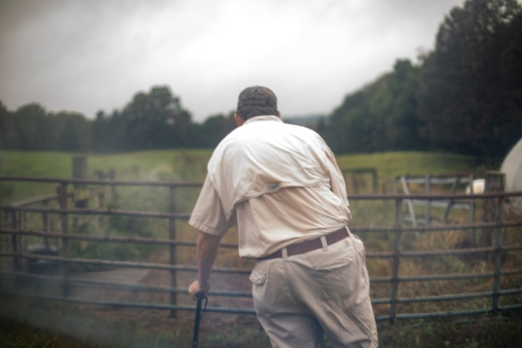 A photo of a farmer leaning on a cane in front of a gate.